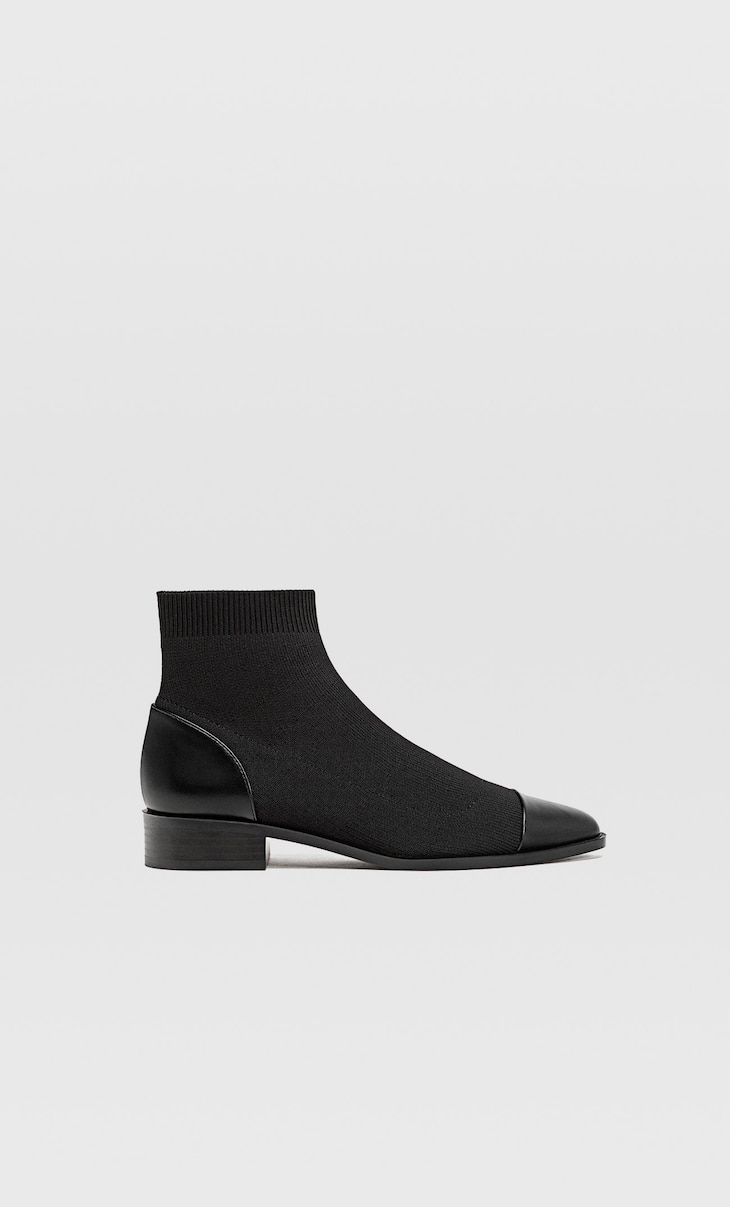 Flat sock-style ankle boots with detailing on the toes